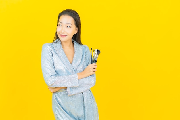 Portrait beautiful young asian woman smile with cosmetic make up brush on yellow wall