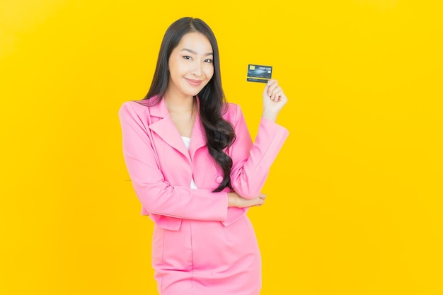 黄色の壁にクレジット カードで笑顔のポートレート美しい若いアジア女性