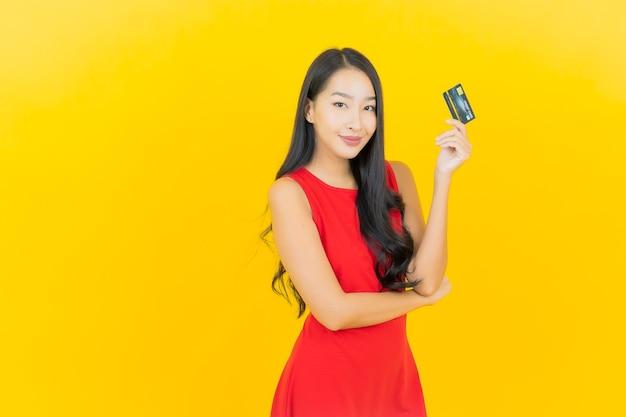 黄色の壁にクレジットカードで笑顔美しい若いアジアの女性の肖像画