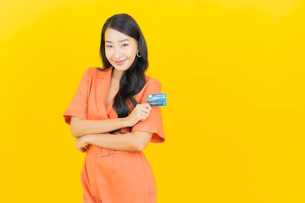 Улыбка женщины портрета красивая молодая азиатская с кредитной картой на желтом Бесплатные Фотографии