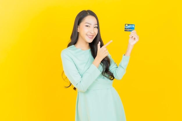 黄色のクレジットカードで笑顔美しい若いアジアの女性の肖像画