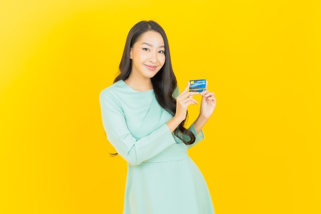 노란색에 신용 카드와 초상화 아름 다운 젊은 아시아 여자 미소
