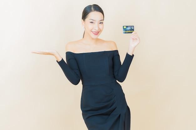 Улыбка женщины портрета красивая молодая азиатская с кредитной картой на желтом