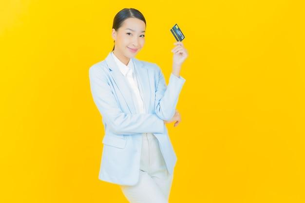 노란색에 신용 카드와 함께 초상화 아름 다운 젊은 아시아 여자 미소