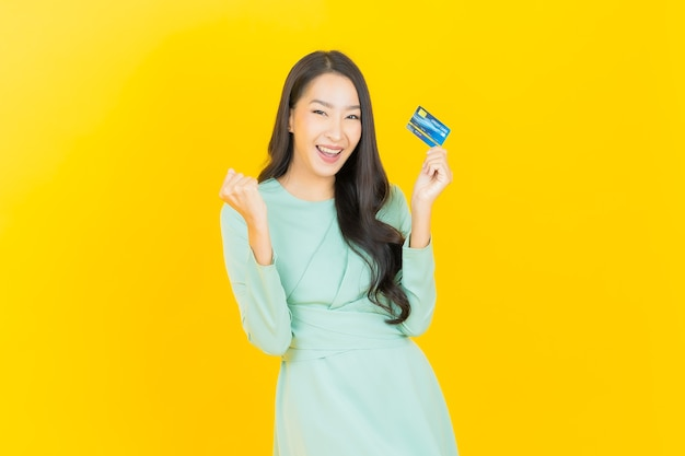 Portrait beautiful young asian woman smile with credit card on yellow