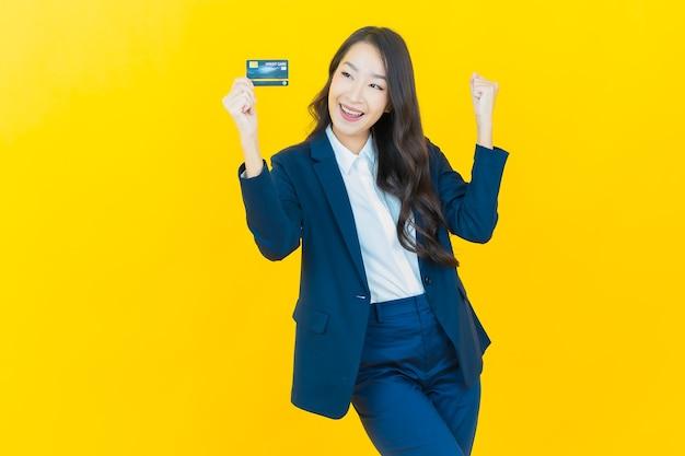 Ritratto bella giovane donna asiatica sorriso con carta di credito su yellow