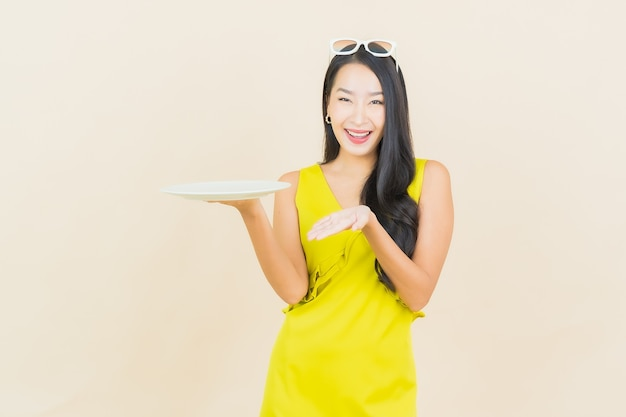 Portrait beautiful young asian woman smile with empty plate dish on color wall