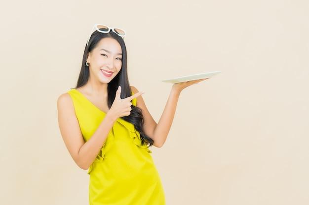 Sorriso della bella giovane donna asiatica del ritratto con il piatto vuoto del piatto sulla parete di colore