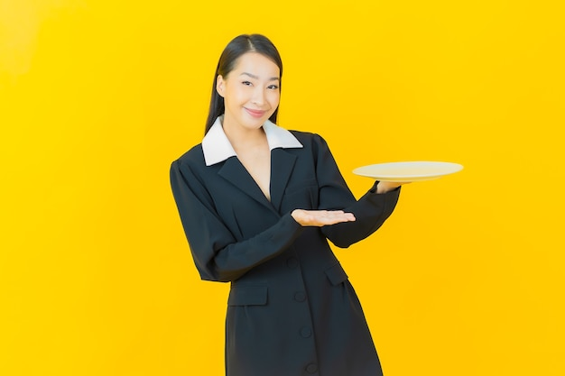 Sorriso di bella giovane donna asiatica del ritratto con il piatto vuoto del piatto sulla parete di colore