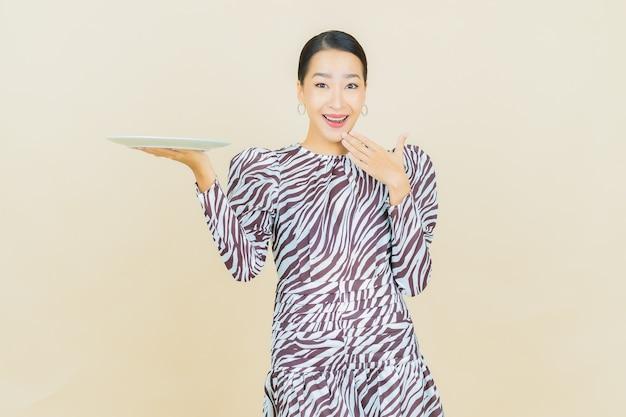 베이지 색에 빈 접시 접시와 세로 아름 다운 젊은 아시아 여자 미소