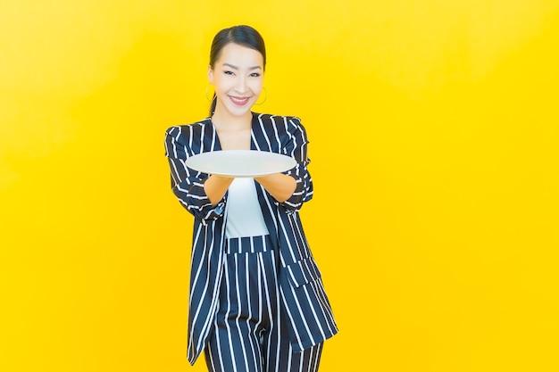 肖像画美しい若いアジアの女性は、色の背景に空の皿皿で笑顔