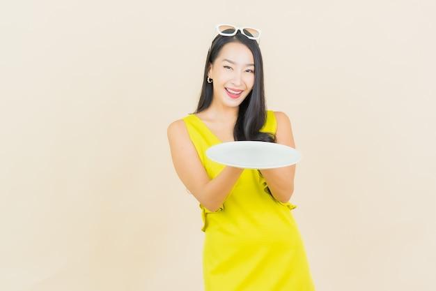세로 아름 다운 젊은 아시아 여자 컬러 벽에 빈 접시 접시와 미소