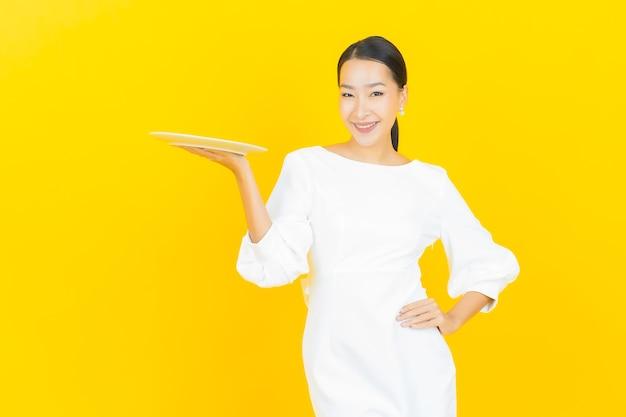 노란색에 빈 접시 접시와 초상화 아름 다운 젊은 아시아 여자 미소