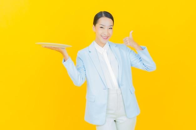 노란색에 빈 접시 접시와 함께 초상화 아름 다운 젊은 아시아 여자 미소