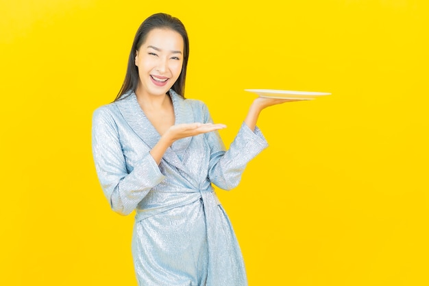 Portrait beautiful young asian woman smile with empty plate dish on yellow wall