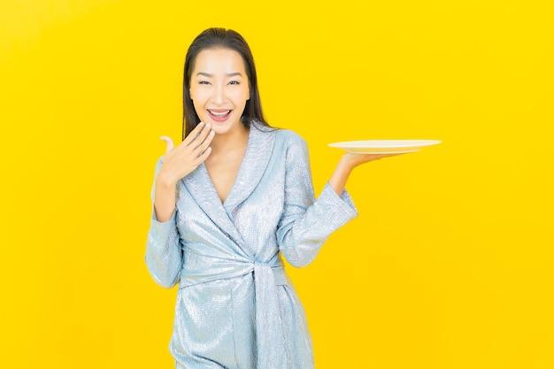 与空的板材盘的画象美丽的年轻亚裔妇女微笑在黄色墙壁上