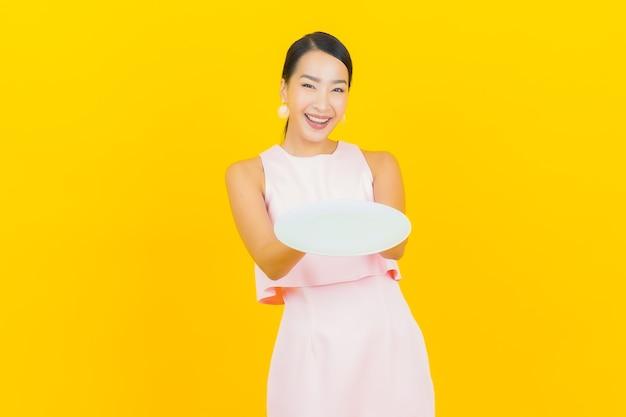 Sorriso della bella giovane donna asiatica del ritratto con il piatto vuoto del piatto su colore giallo