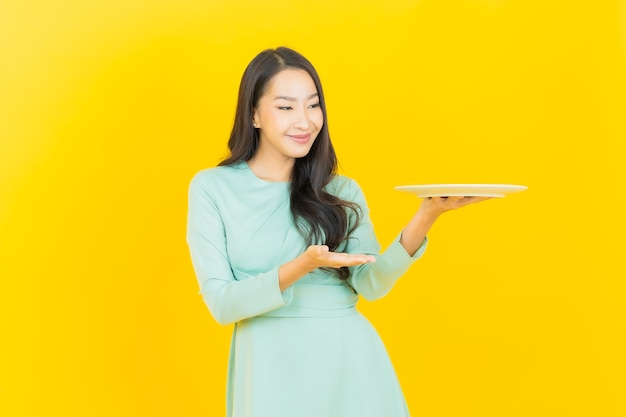 Portrait beautiful young asian woman smile with empty plate dish on yellow Premium Photo
