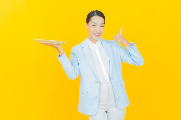 Portrait beautiful young asian woman smile with empty plate dish on yellow