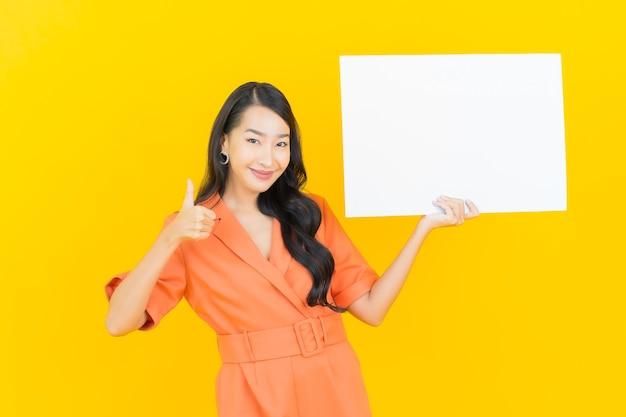 黄色の空の白い看板と肖像画美しい若いアジアの女性の笑顔