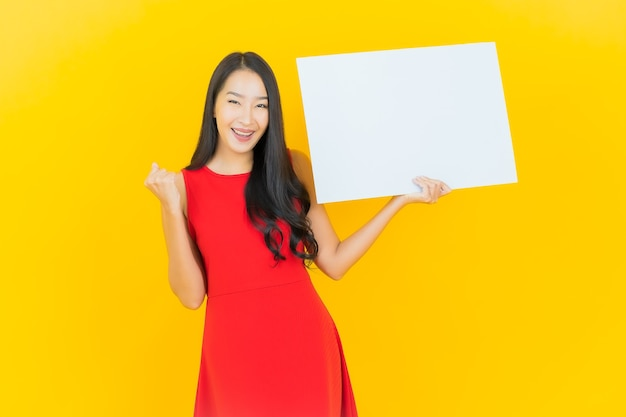 Portrait beautiful young asian woman smile with empty white billboard on yellow wall