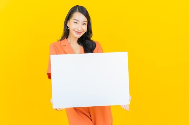 Sorriso della bella giovane donna asiatica del ritratto con il tabellone per le affissioni bianco vuoto su colore giallo