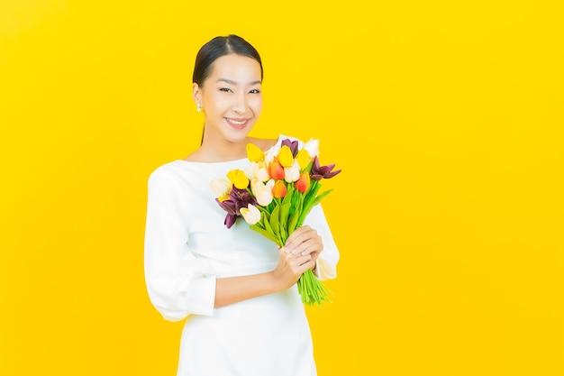 Улыбка женщины портрета красивая молодая азиатская с цветком на желтом