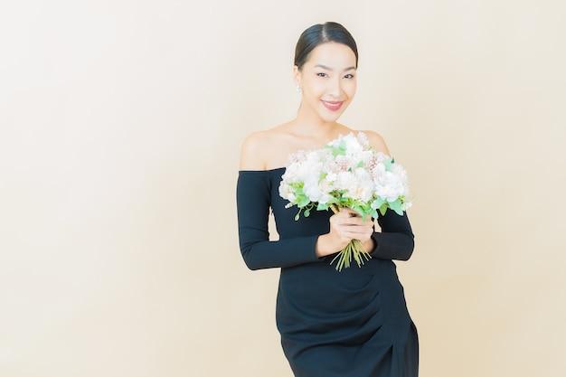 Sorriso di bella giovane donna asiatica del ritratto con il fiore su yellow