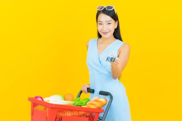Улыбка женщины портрета красивая молодая азиатская с продуктовой корзиной от супермаркета на стене желтого цвета