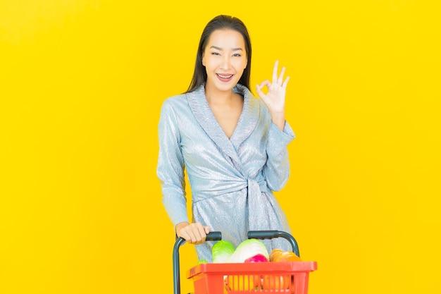 黄色の壁にスーパーマーケットから食料品バスケットと肖像画美しい若いアジアの女性の笑顔