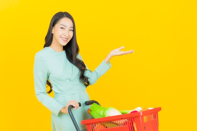 노란색 슈퍼마켓에서 식료품 바구니와 세로 아름 다운 젊은 아시아 여자 미소