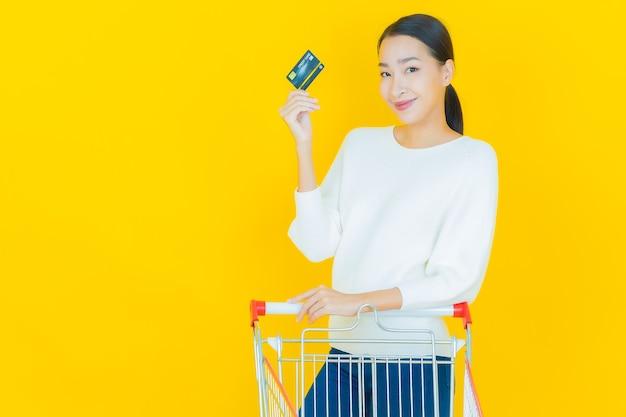 노란색 슈퍼마켓에서 식료품 바구니를 들고 웃는 아름다운 젊은 아시아 여성