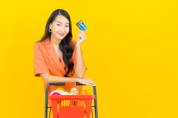 Portrait beautiful young asian woman smile with grocery basket from supermarket on yellow