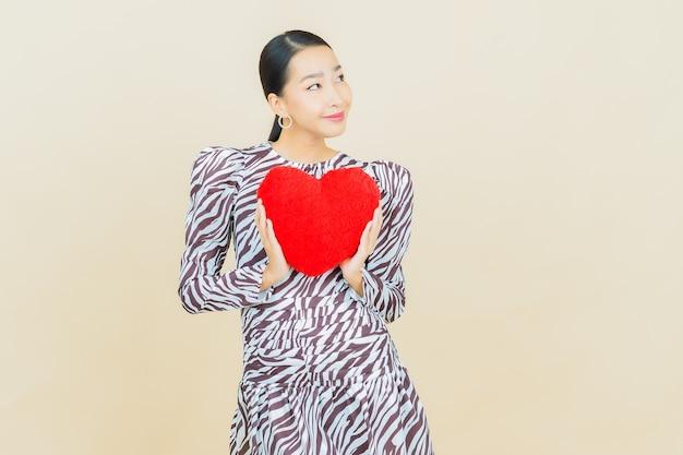Улыбка женщины портрета красивая молодая азиатская с формой подушки сердца на бежевом