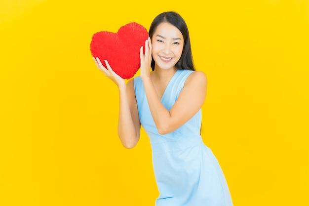 Улыбка женщины портрета красивая молодая азиатская с формой подушки сердца на стене желтого цвета