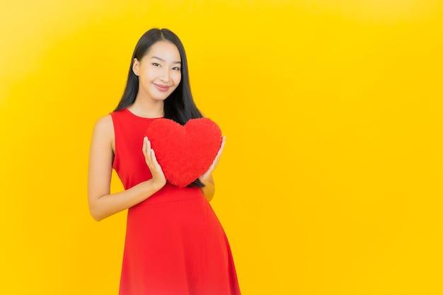 Sorriso della bella giovane donna asiatica del ritratto con forma del cuscino del cuore sulla parete gialla