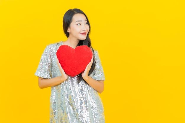 Sorriso di bella giovane donna asiatica del ritratto con forma di cuscino cuore su giallo