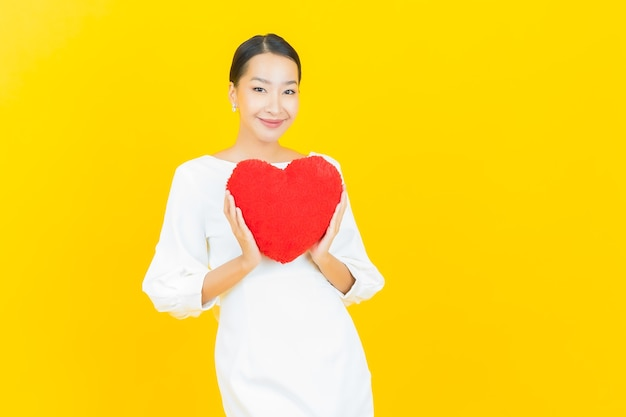 Portrait beautiful young asian woman smile with heart pillow shape on yellow