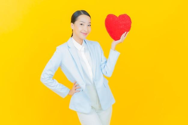 Sorriso di bella giovane donna asiatica del ritratto con la forma del cuscino del cuore su yellow