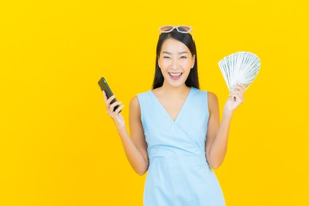 Portrait beautiful young asian woman smile with a lot of cash and money on yellow color wall