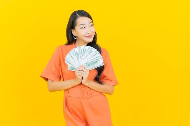 Sorriso della bella giovane donna asiatica del ritratto con molti contanti e soldi su colore giallo