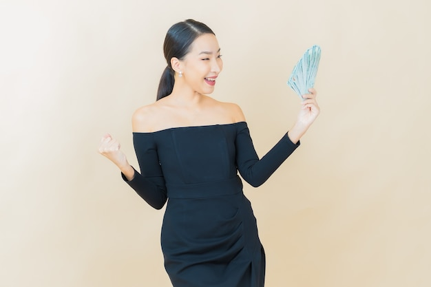Portrait beautiful young asian woman smile with a lot of cash and money on yellow