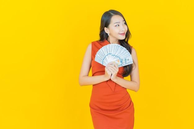 La bella giovane donna asiatica del ritratto sorride con molti contanti e soldi su yellow