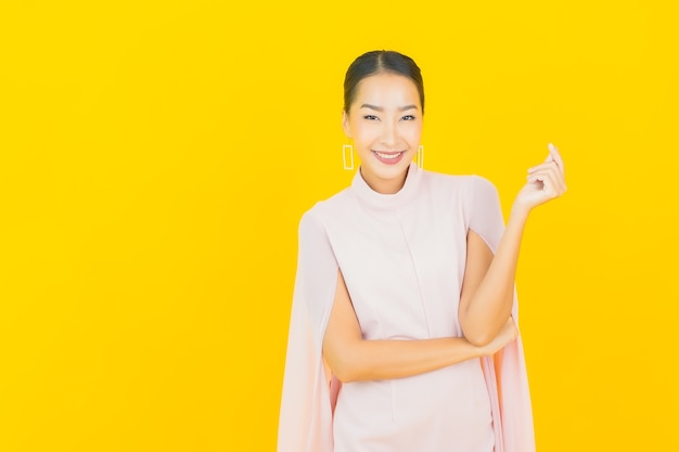 黄色の壁に多くのアクションと肖像画美しい若いアジアの女性の笑顔