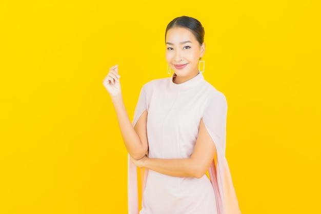 노란색 벽에 많은 조치와 초상화 아름 다운 젊은 아시아 여자 미소