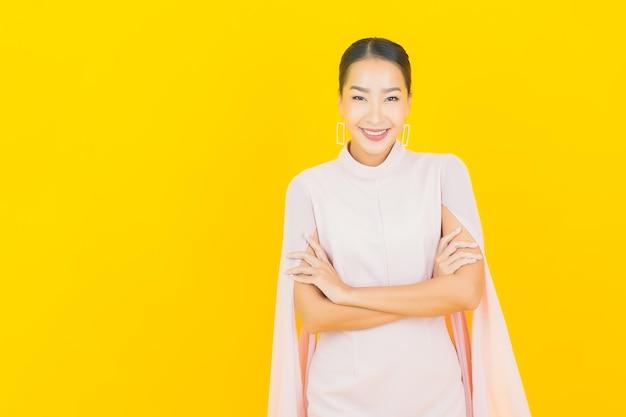 Sorriso di bella giovane donna asiatica del ritratto con molte azioni sulla parete gialla