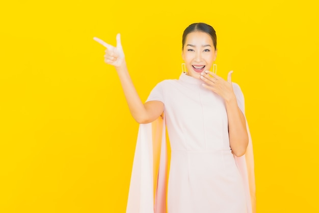 Portrait beautiful young asian woman smile with many action on yellow wall