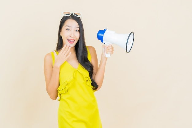 Portrait beautiful young asian woman smile with megaphone on color wall