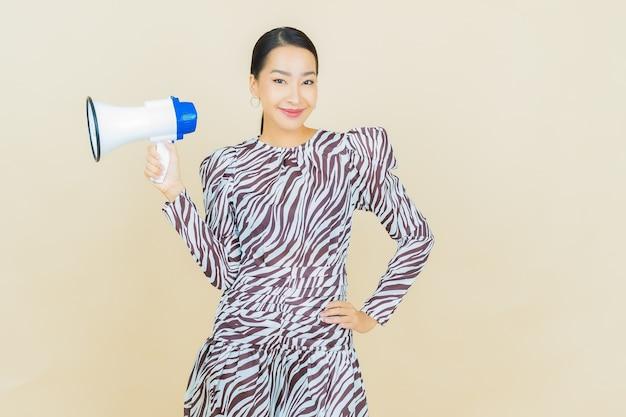 베이지 색에 확성기와 세로 아름 다운 젊은 아시아 여자 미소