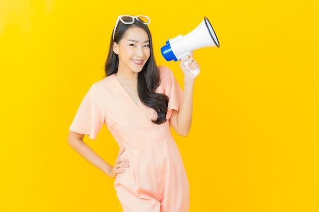 컬러 벽에 확성기와 미소 초상화 아름 다운 젊은 아시아 여자